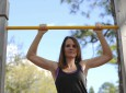 young stong woman doing pull ups outdoors